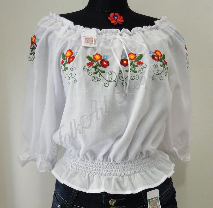 287. Vállra lehúzható, gumis derekú, rövid fazonú hímzett blúz,  fehér alapon színes virágos mintával